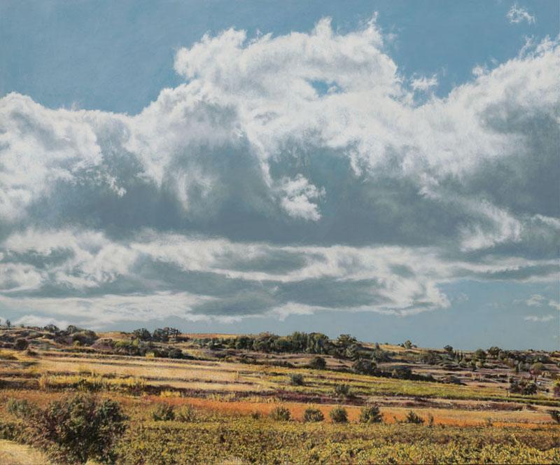 Herbstliche Landschaft mit orange leuchtenden Weinbergszeilen und niedrigem Horizont. Darüber schwebt eine Haufenwolke in türkisblauem Himmel.