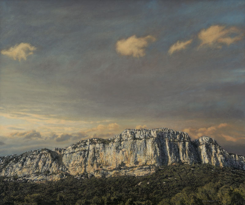 Der Berg Hortus mit Wald im Vordergrund in südfranzösischem Abendlicht befindet sich im unteren Drittel des Bildes. Drei kleine gelborange leuchtende Wattewölkchen beleben das obere Drittel des Abendhimmels.