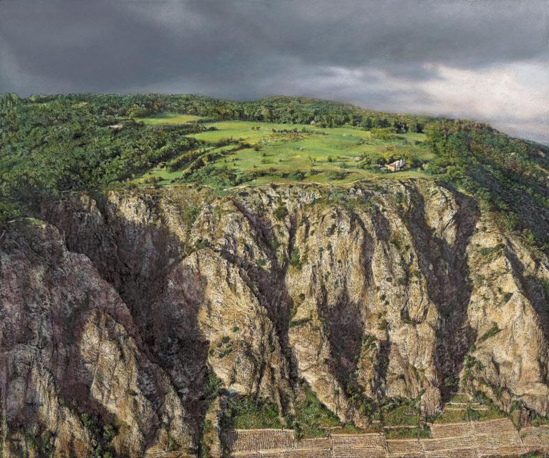 Frühlingshafter Rotenfels mit leuchtend grünem Plateau vom Flugzeug aus gesehen. Eine graublaue Gewitterwolke befindet sich im oberen Viertel des Bildes.