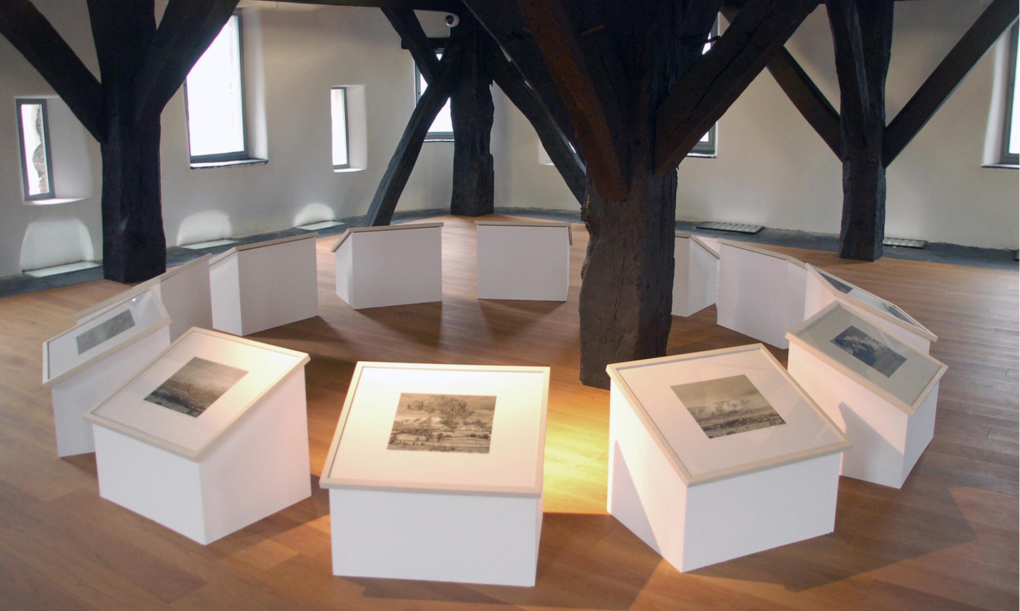 Zwölf weiße Holzobjekte mit schwarzweißen Grafiken auf einem Holzfußboden im Kreis. Sie befinden sich im Turmzimmer des Museums Boppard.